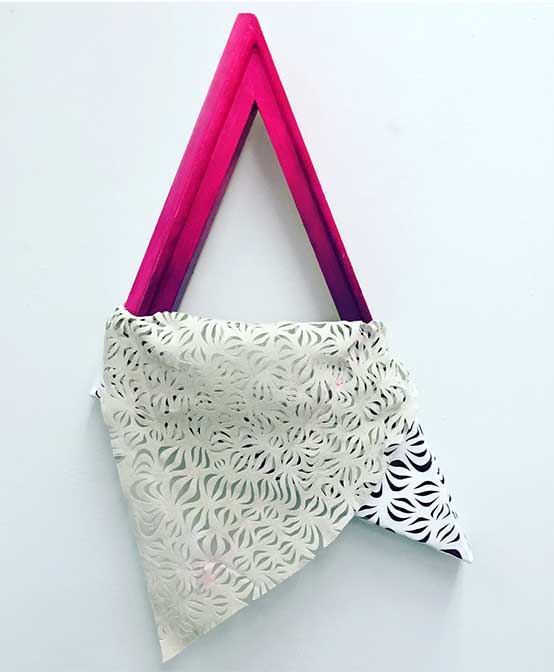 a lace fabric folded over a pink triangle frame