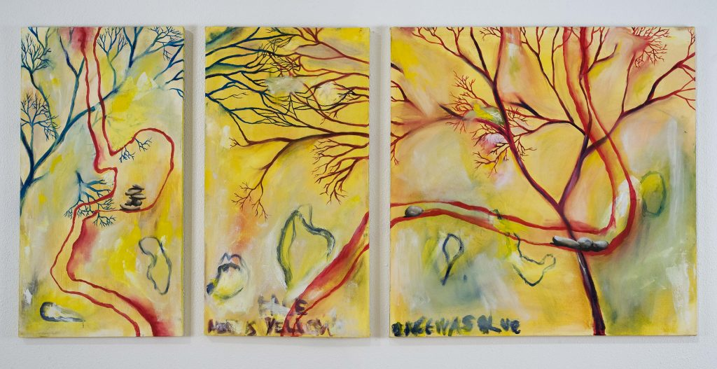 leafless tree limbs stretch across three canvasses