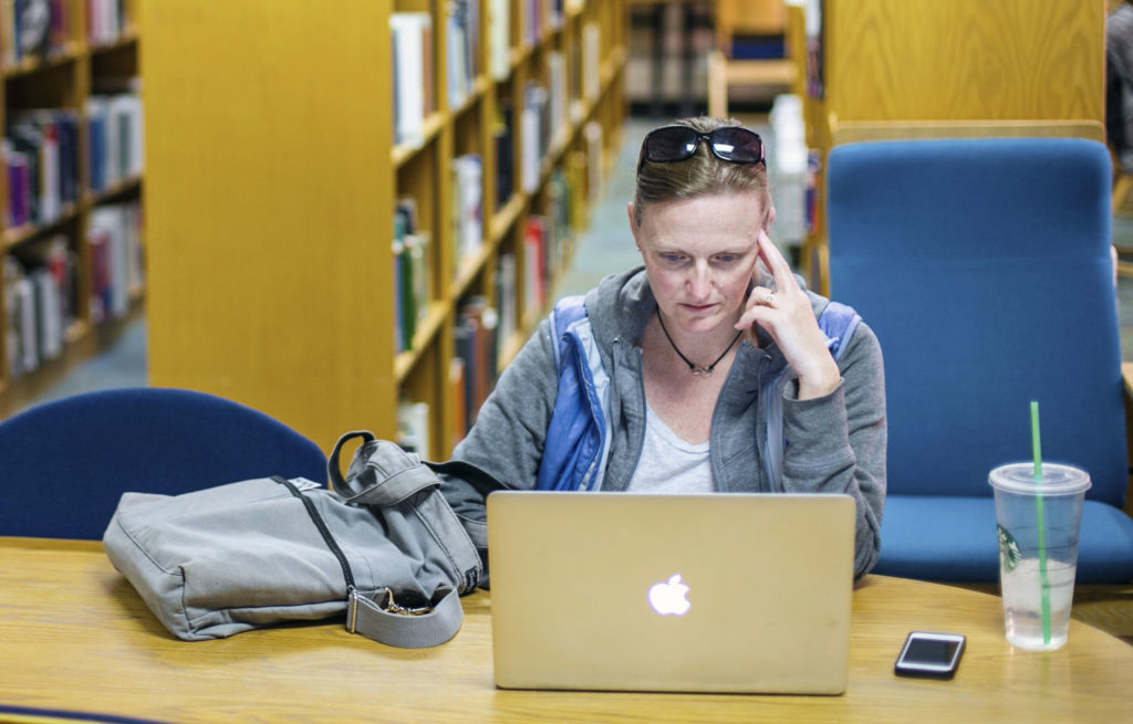 a woman working on a laptop in the library