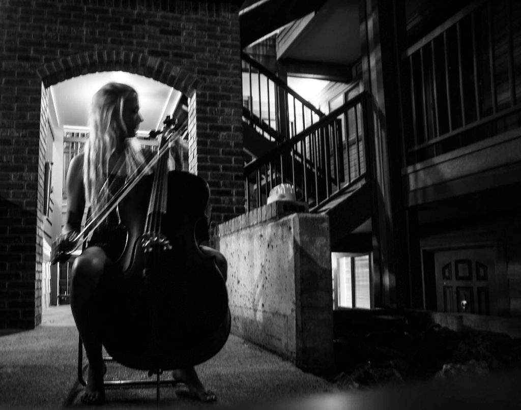 A black and white photo of a woman playing cello