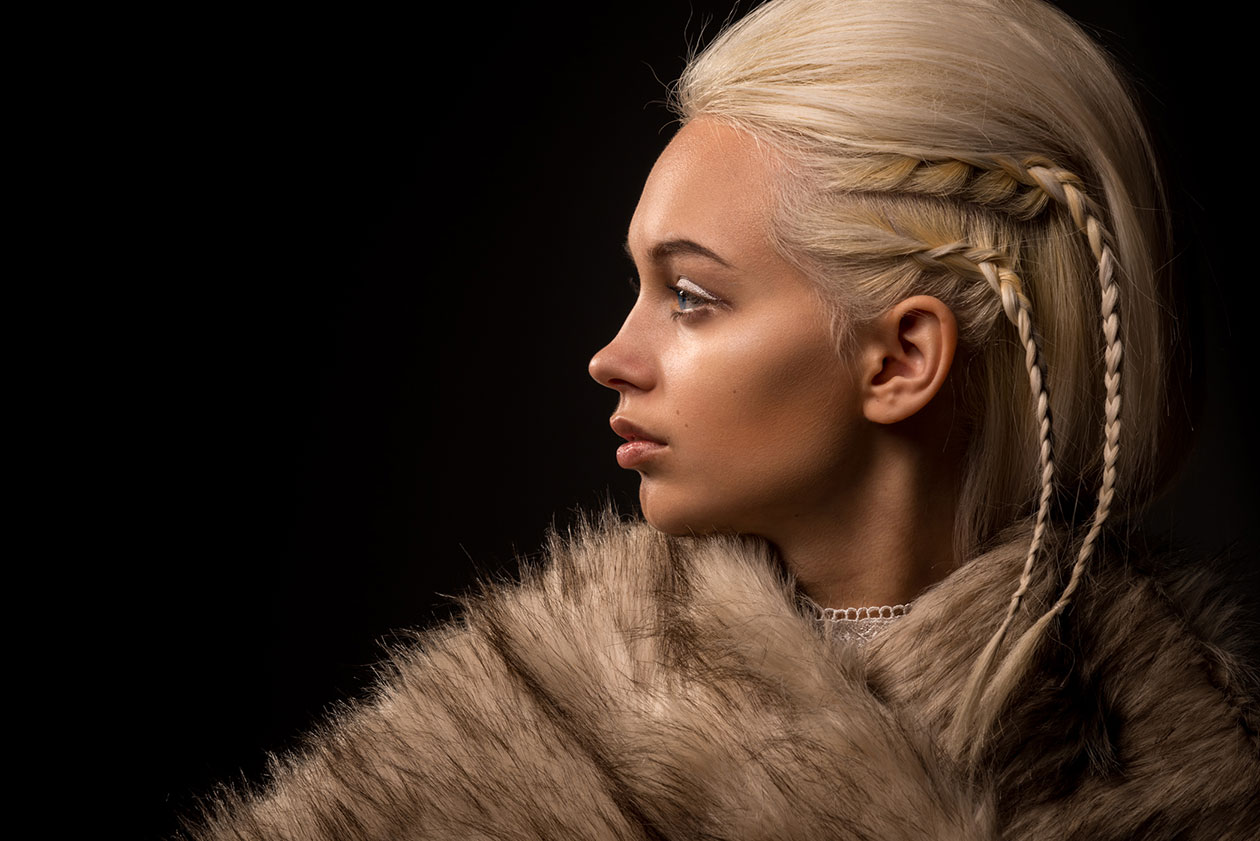 A photo of a blond woman profile in furs and braids
