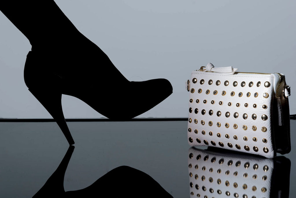 stiletto silhouette next to designer handbag