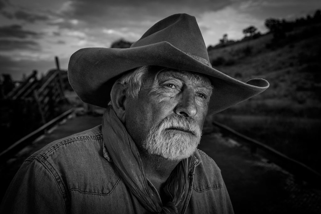 Black and white photo of an elderly man in a cowboy hat