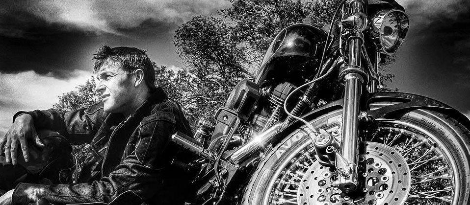 black and white art photo of a man seated on the ground next to a motorcycle