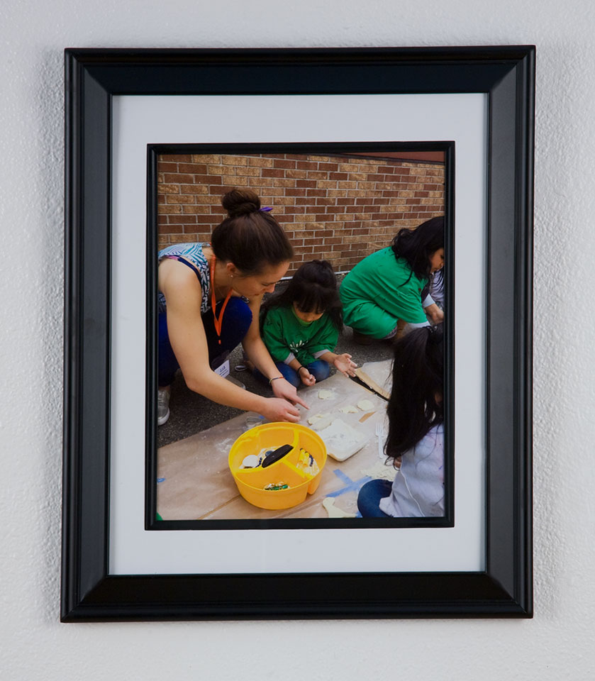 A picture of a framed photo of a woman painting with children